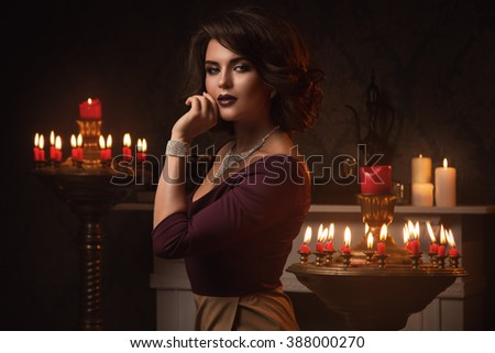 Portrait of beautiful woman in room with a lot of candles