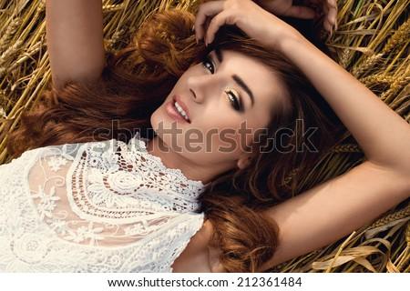 portrait of beautiful woman in rye field wearing white dress. Rural lifestyle - stock photo