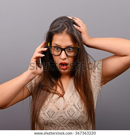 Portrait of beautiful woman in shock while talking on  a cellphone against gray background - stock photo