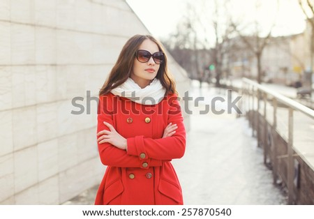 Portrait of beautiful woman in sunglasses and red jacket outdoors