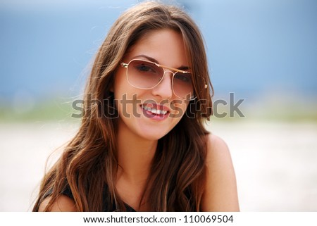 Portrait of beautiful woman in sunglasses on the beach - stock photo