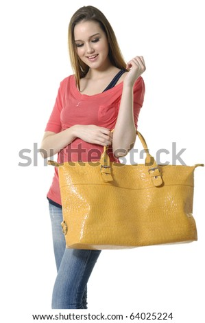 portrait of beautiful woman in t-shirt and jeans holding handbag - stock photo