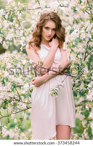 Portrait of beautiful woman in the flowering park - stock photo