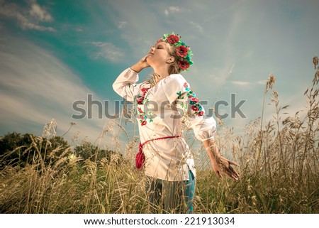 Portrait of beautiful woman in ukrainian clothes at field at windy day - stock photo