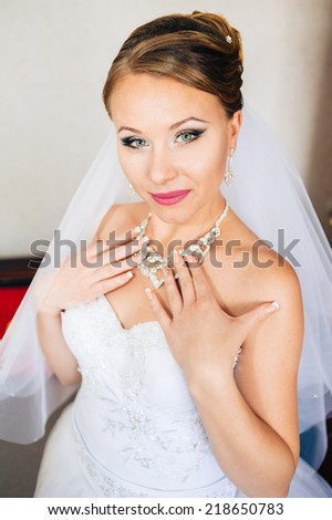 Portrait of beautiful woman in white dress. adorable bride is getting ready in the morning. Adorable young bride is getting ready in the morning at home.