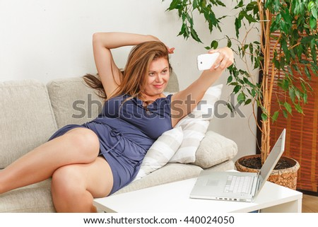 Portrait of beautiful woman making selfie at home. Beautiful and pretty lady with red hair lying on sofa or couch. - stock photo