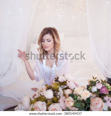 Portrait of beautiful woman model with fresh daily makeup and romantic wavy hairstyle. Girl received flowers as a gift