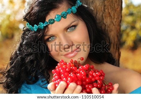 Portrait of beautiful Woman on rest with berry in her hands - stock photo
