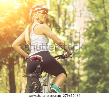 Portrait of beautiful woman on the bicycle in the park. - stock photo