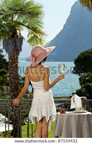 portrait of beautiful woman on the terrace of prestigious hotel back view