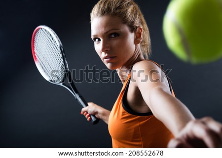 Portrait of beautiful woman playing tennis indoor. Isolated on black. - stock photo