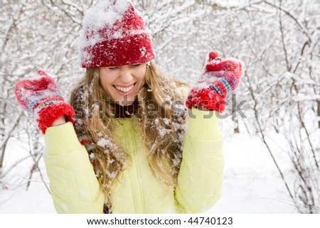 Portrait of beautiful woman screw up her eyes during play in snowballs - stock photo