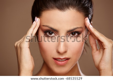 Portrait of beautiful woman, she has migraine, isolated on beige