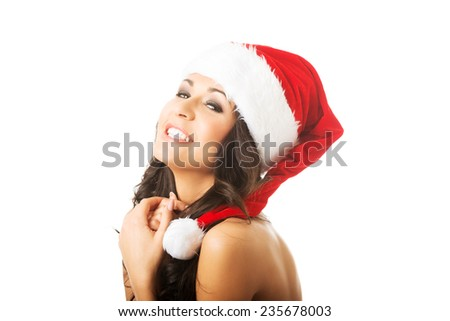 Portrait of beautiful woman shirtless wearing santa claus hat, looking at the camera.