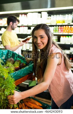 Portrait of beautiful woman shopping for fresh vegetables in supermarket