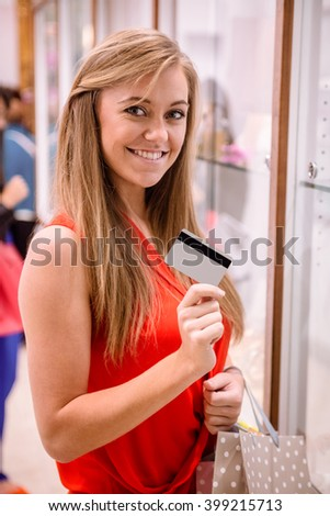 Portrait of beautiful woman showing her credit card while shopping in a jeweler shop