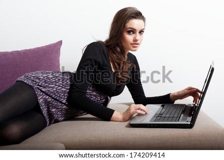 Portrait of beautiful woman sitting at sofa and using laptop looking at camera .Fashion photo.  - stock photo