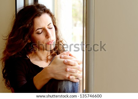 Portrait of beautiful woman sitting on the window - stock photo