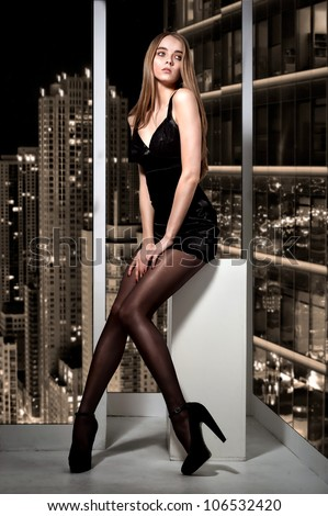 Portrait of beautiful woman sitting on window and looking on night city - stock photo