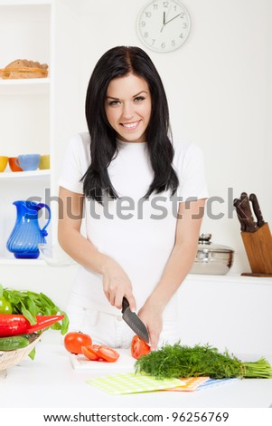 portrait of beautiful woman slice, cutting tomato in the kitchen, cooking, prepare  vegetable salad, looking at camera happy smile - stock photo
