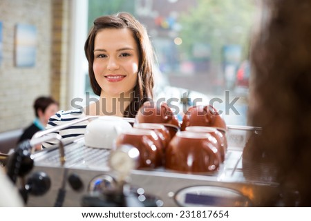 Portrait of beautiful woman standing at counter in coffeeshop - stock photo
