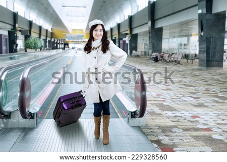 Portrait of beautiful woman standing in the airport hallway while wearing winter coat and carrying luggage - stock photo
