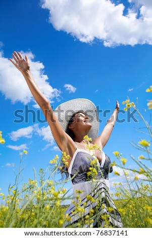 Portrait of beautiful woman standing in the middle of meadow and looking upwards with raised arms