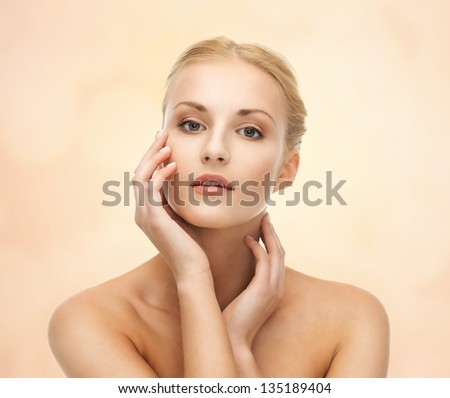portrait of beautiful woman touching her face - stock photo