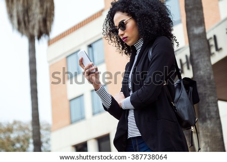 Portrait of beautiful woman using her mobile phone in the street.