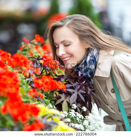 Portrait of beautiful woman walking in the street and smelling flowers