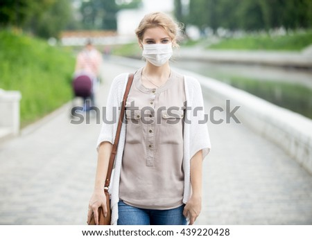 Portrait of beautiful woman walking on the street wearing protective mask as protection against infectious diseases. Attractive unhappy model with flu outdoors. Incidental people on the background - stock photo