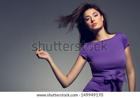 portrait of beautiful woman wearing purple dress. studio shoot. - stock photo