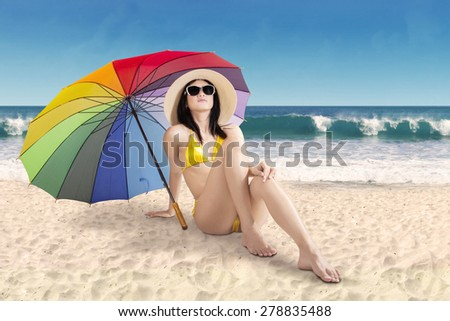 Portrait of beautiful woman wearing swimwear sitting on sand under a rainbow umbrella at coast - stock photo
