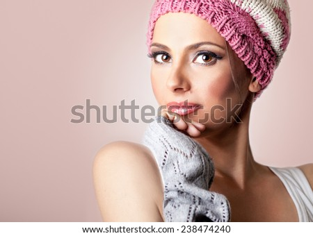 Portrait of beautiful woman wearing winter cap and gloves, on pink background, studio shoot. - stock photo