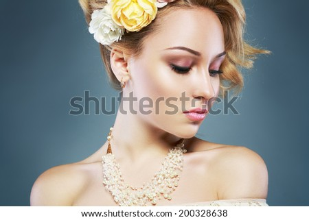 Portrait of Beautiful Woman Wedding Model over Blue Background. Advertising and Commercial Design. Shopping. Perfect Hairstyle with fresh flowers - stock photo
