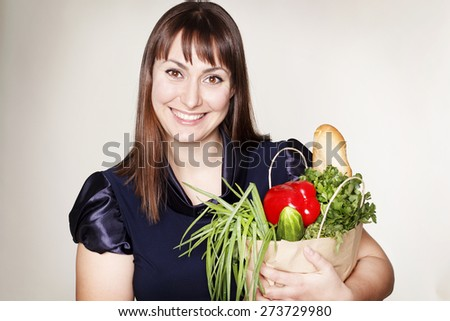Portrait of beautiful woman with a bag of products over grey background - stock photo