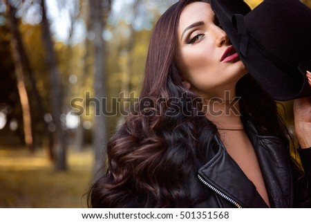 portrait of beautiful woman with amazing natural hair style with hat near eyes in the autumn park