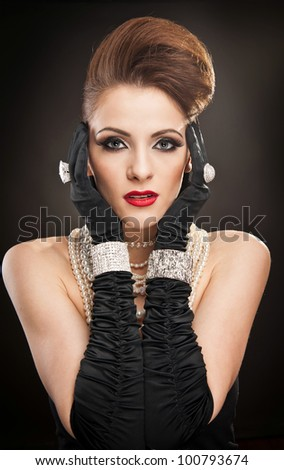 portrait of beautiful woman with beads and  black long gloves isolated on black - stock photo