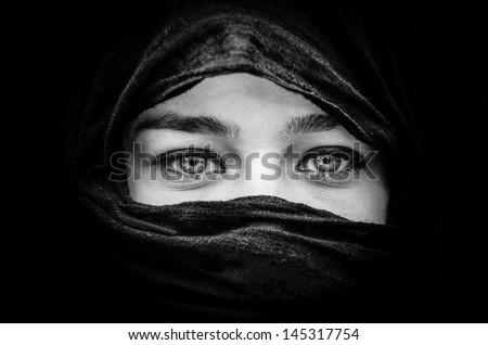 Portrait of beautiful woman with blue eyes wearing black scarf in black and white - stock photo