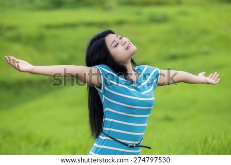 Portrait of beautiful woman with casual clothes, enjoy freedom while breathe fresh air on the green meadow - stock photo