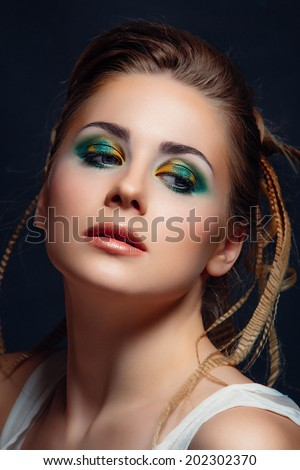 portrait of beautiful woman with color make-up on green background