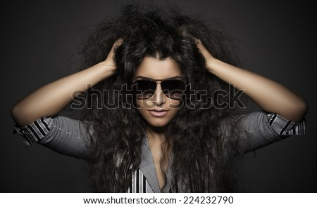 Portrait of beautiful woman with curly hairs and glasses, on dark background - stock photo