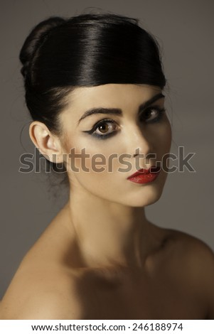 Portrait of beautiful woman with dark and dramatic makeup around her brown eyes, wearing red lip stick and her hair in an up do. - stock photo