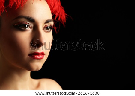 Portrait of beautiful woman with fancy glitter makeup and red feather on dark background