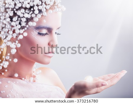 Portrait of beautiful woman with fantasy make-up with hair of white pearls on a light background - stock photo