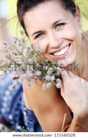 Portrait of beautiful woman with field plant in hands - stock photo