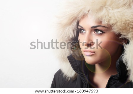 Portrait of beautiful woman with fur. white fur hood. winter style.your text here.