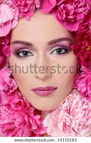 Portrait of beautiful woman with glamorous makeup and peonies around her face