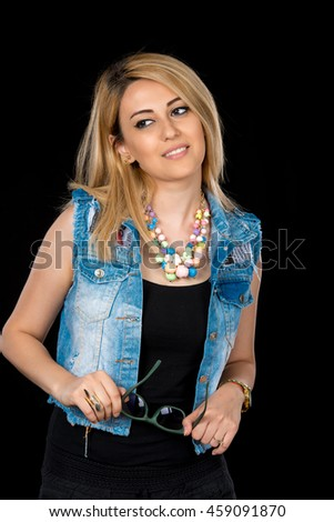Portrait of beautiful woman with glasses in black clothes and blue jeans  on black background