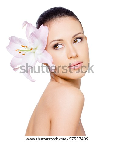 Portrait of beautiful woman with healthy skin with flower in her hair